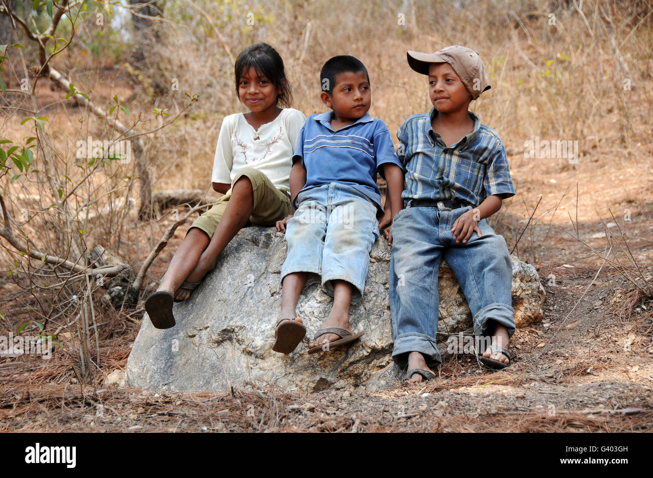 Guatemalan children sitting on a rock in El Robles, Guatemala. - Stock Image