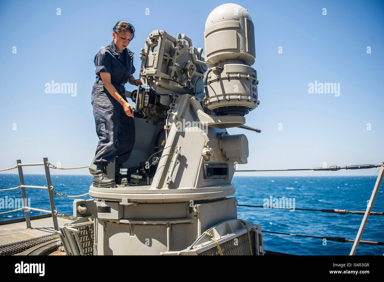 Seaman performs maintenance on a Mark 38 MOD 2 25mm machine gun/ - Stock Image