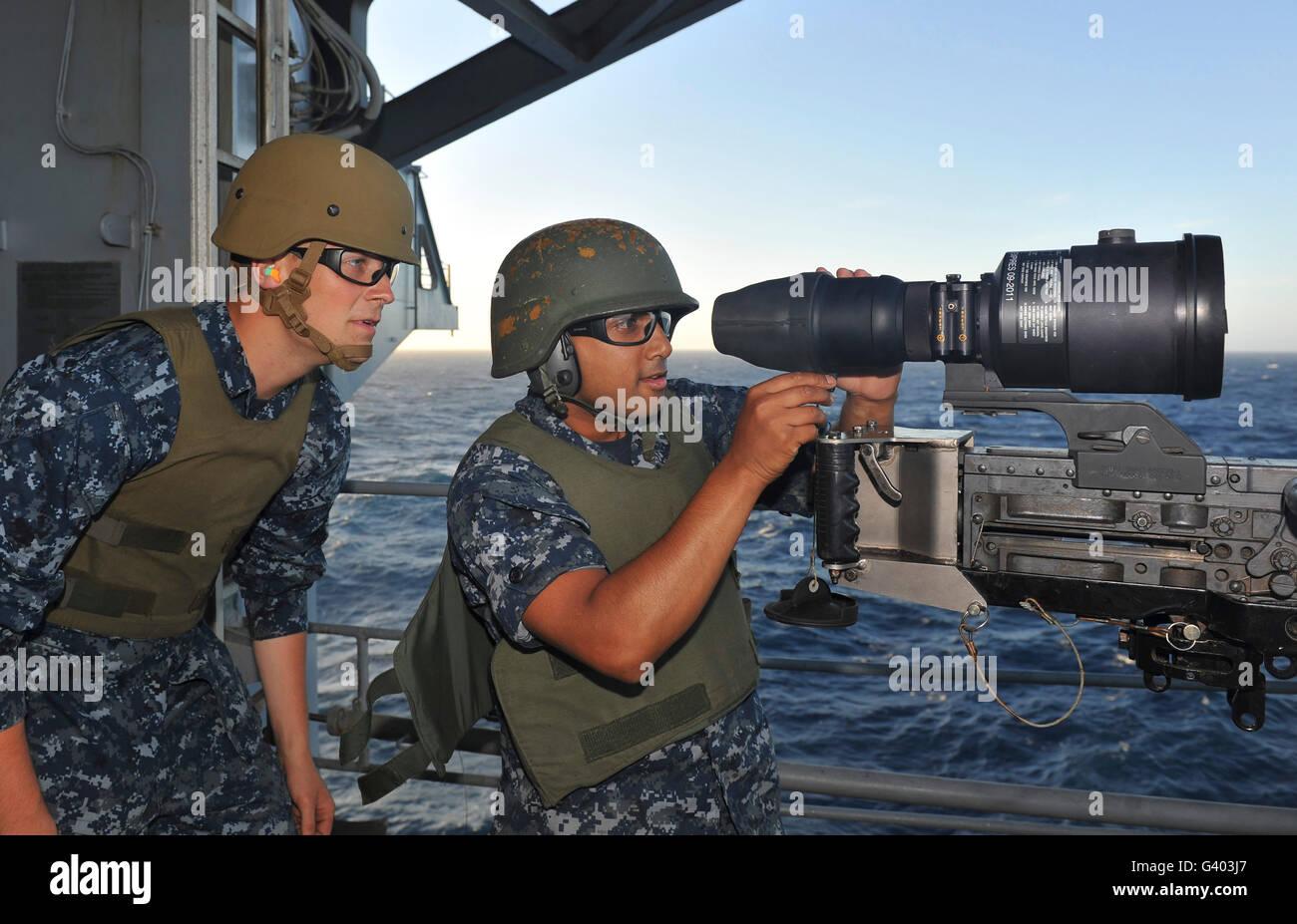 Airmen adjust a night vision scope on a .50-caliber machine gun. - Stock Image