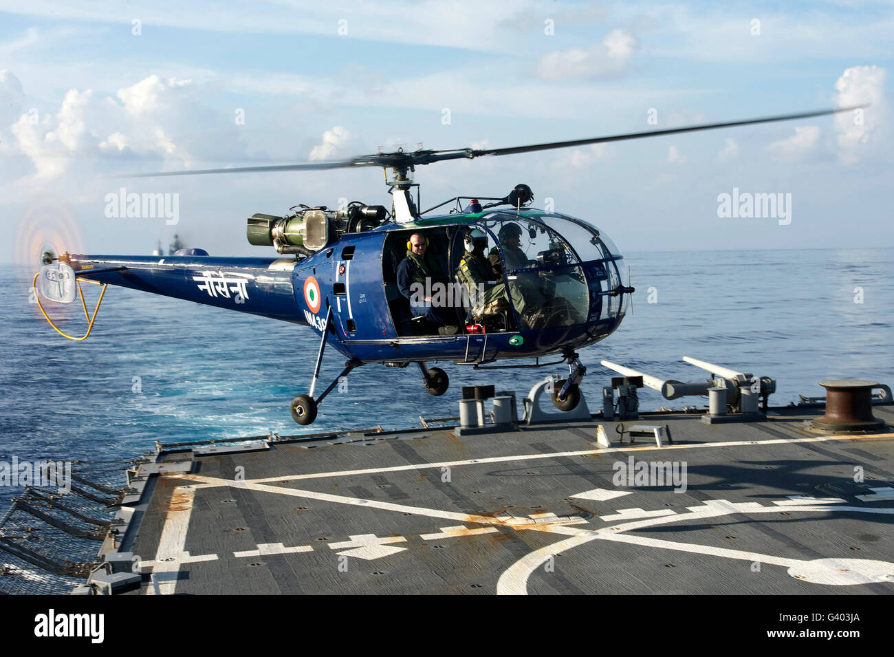 An Indian Navy helicopter  lands on the flight deck of USS John S. McCain. - Stock Image
