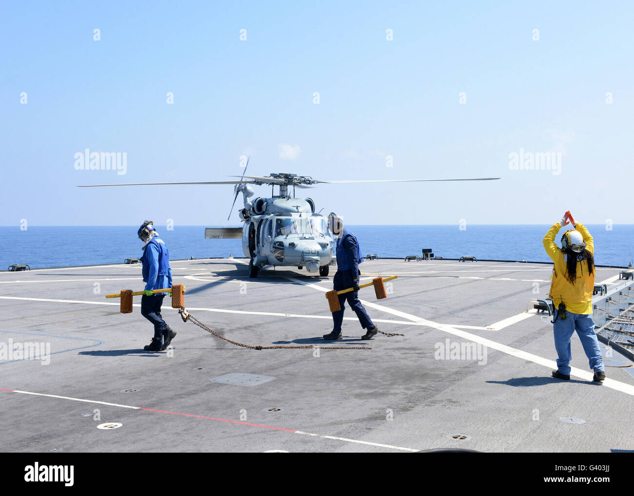 A civil service mariner directs an MH-60S Sea Hawk aboard USS Mount Whitney. - Stock Image