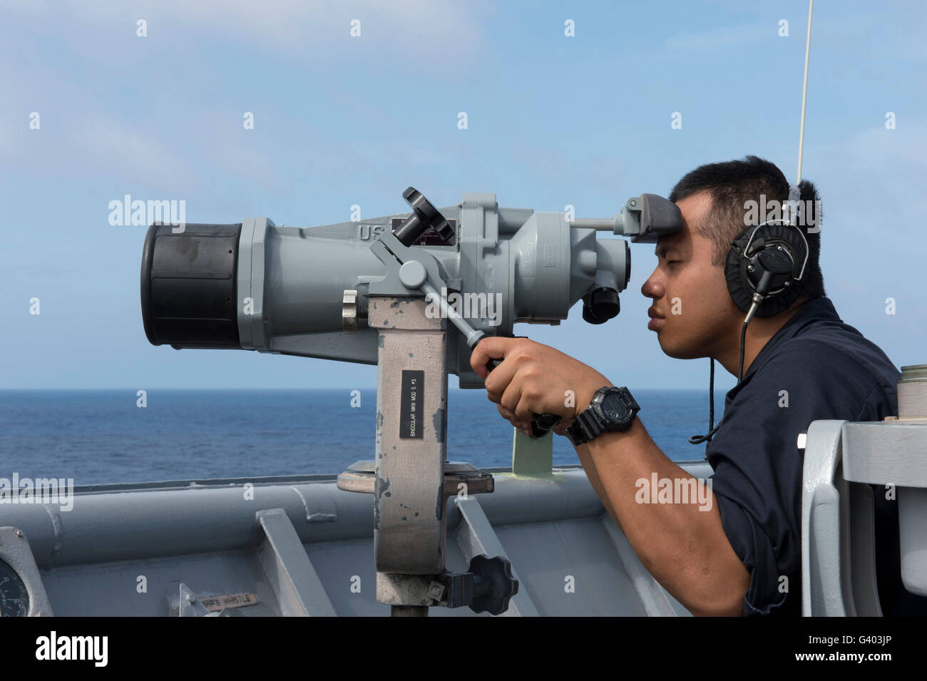 Seaman looks for surface contacts aboard USS Germantown. - Stock Image