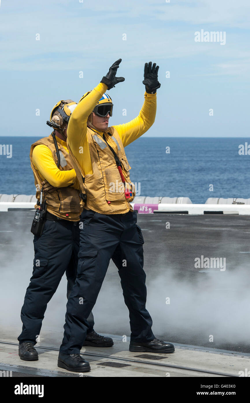 Aviation Boatswain's Mate directs an aircraft onto a catapult. - Stock Image