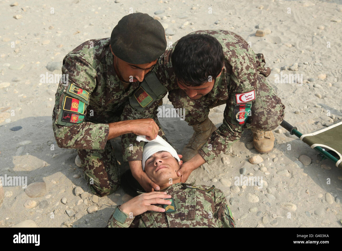 Afghan National Army soldiers put a head bandage on a fellow soldier. - Stock Image