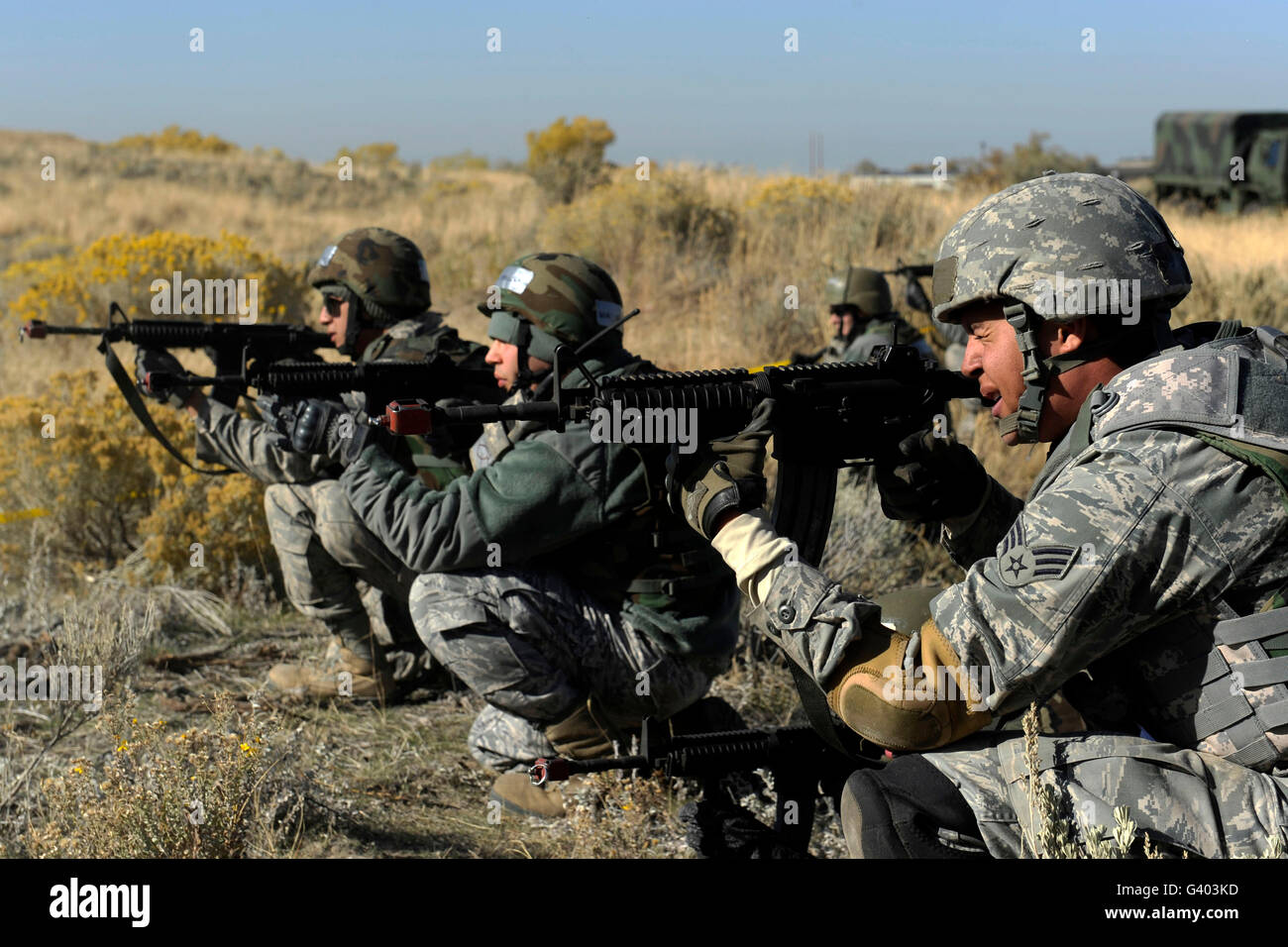 U.S. Airmen fire blanks against simulated enemy forces. - Stock Image