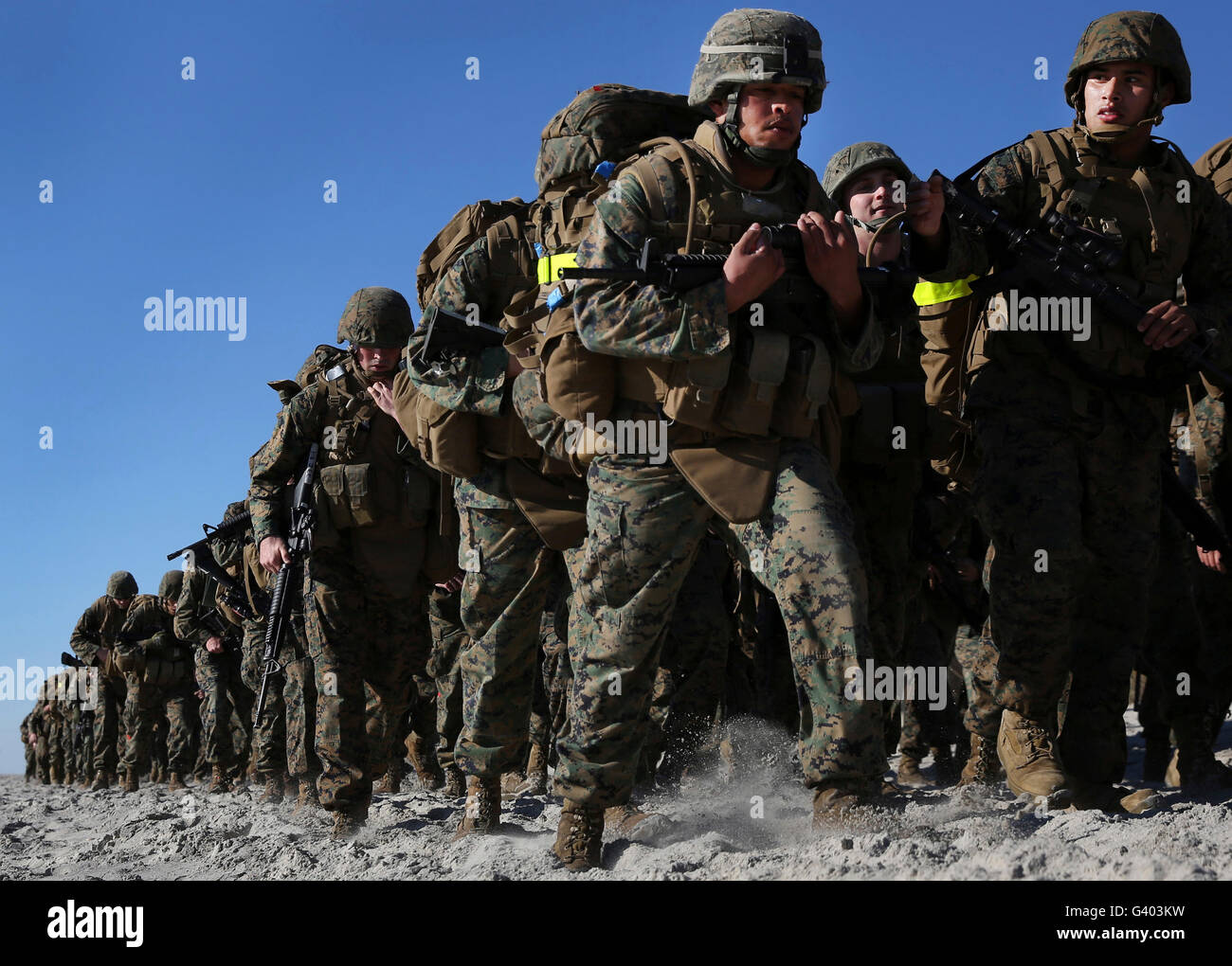 Marines and sailors tramp through the sands of Onslow Beach. - Stock Image