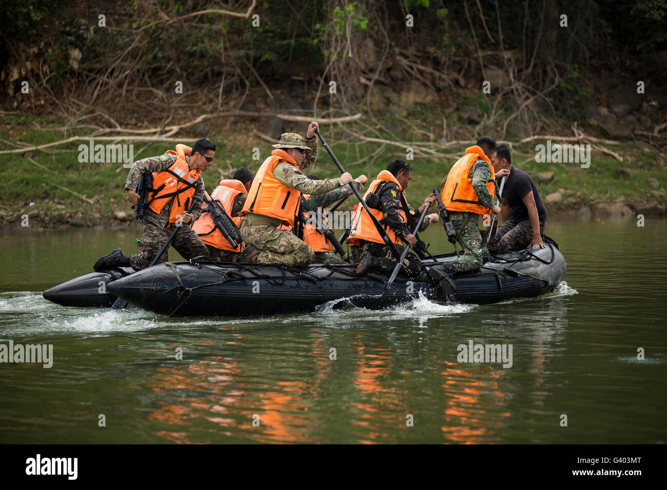 Philippine and U.S. special operations forces soldiers paddle a river. - Stock Image