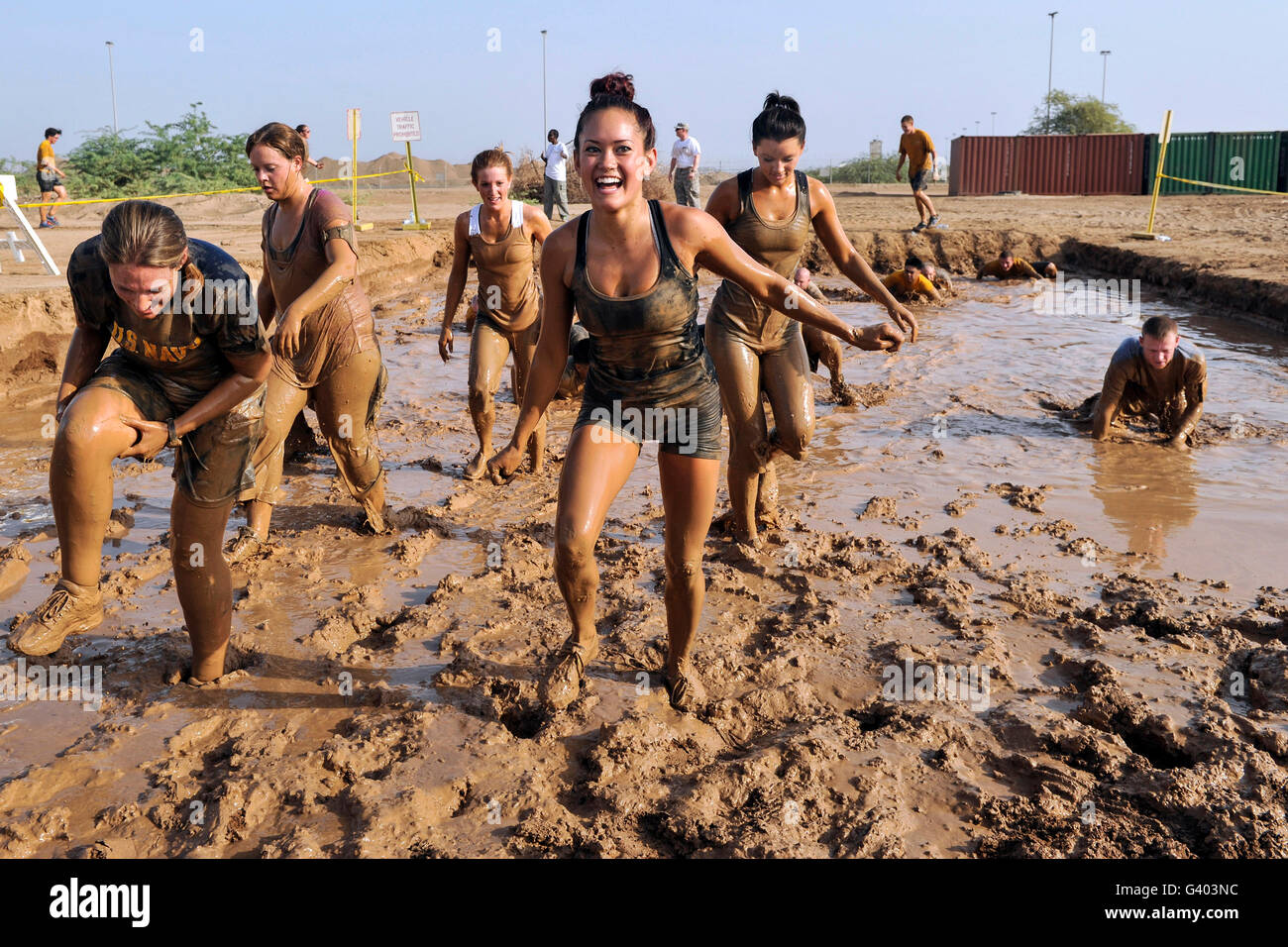 Competitors emerge from a mud pit at Camp Lemonnier, Djibouti. - Stock Image