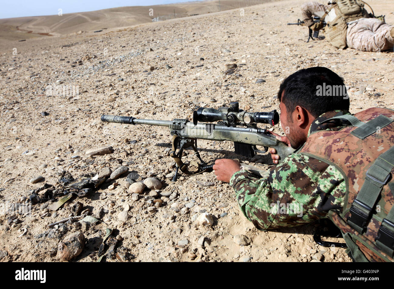 An Afghan National Army soldier fires an M40A5 rifle. - Stock Image
