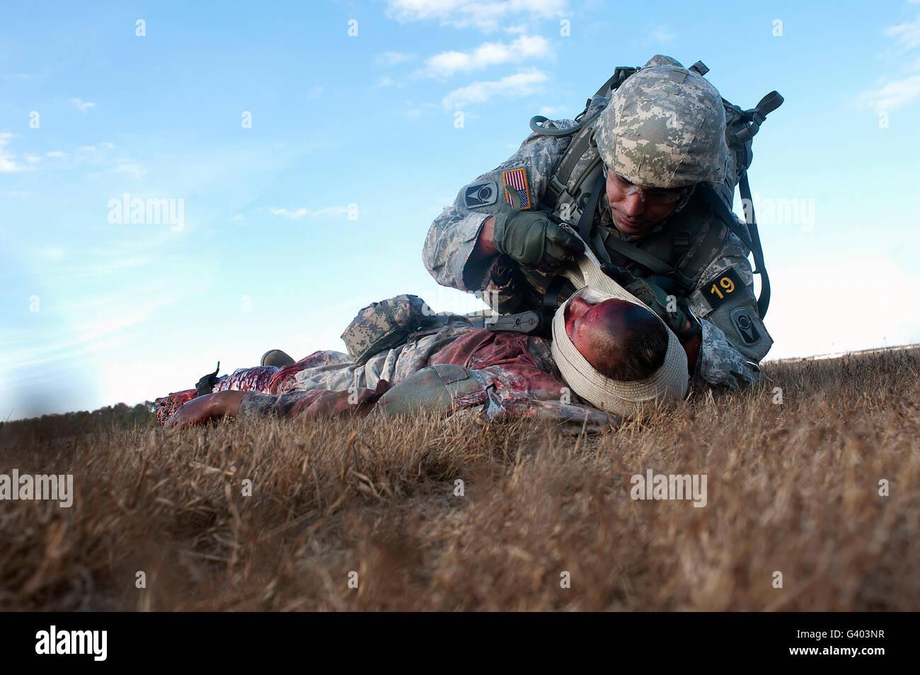 U.S. Army infantryman bandages an injured soldier. - Stock Image