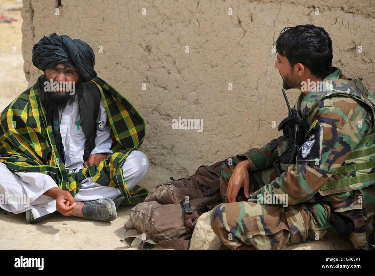 A commando from 3rd Special Operations Kandak speaks with a local villager. - Stock Image