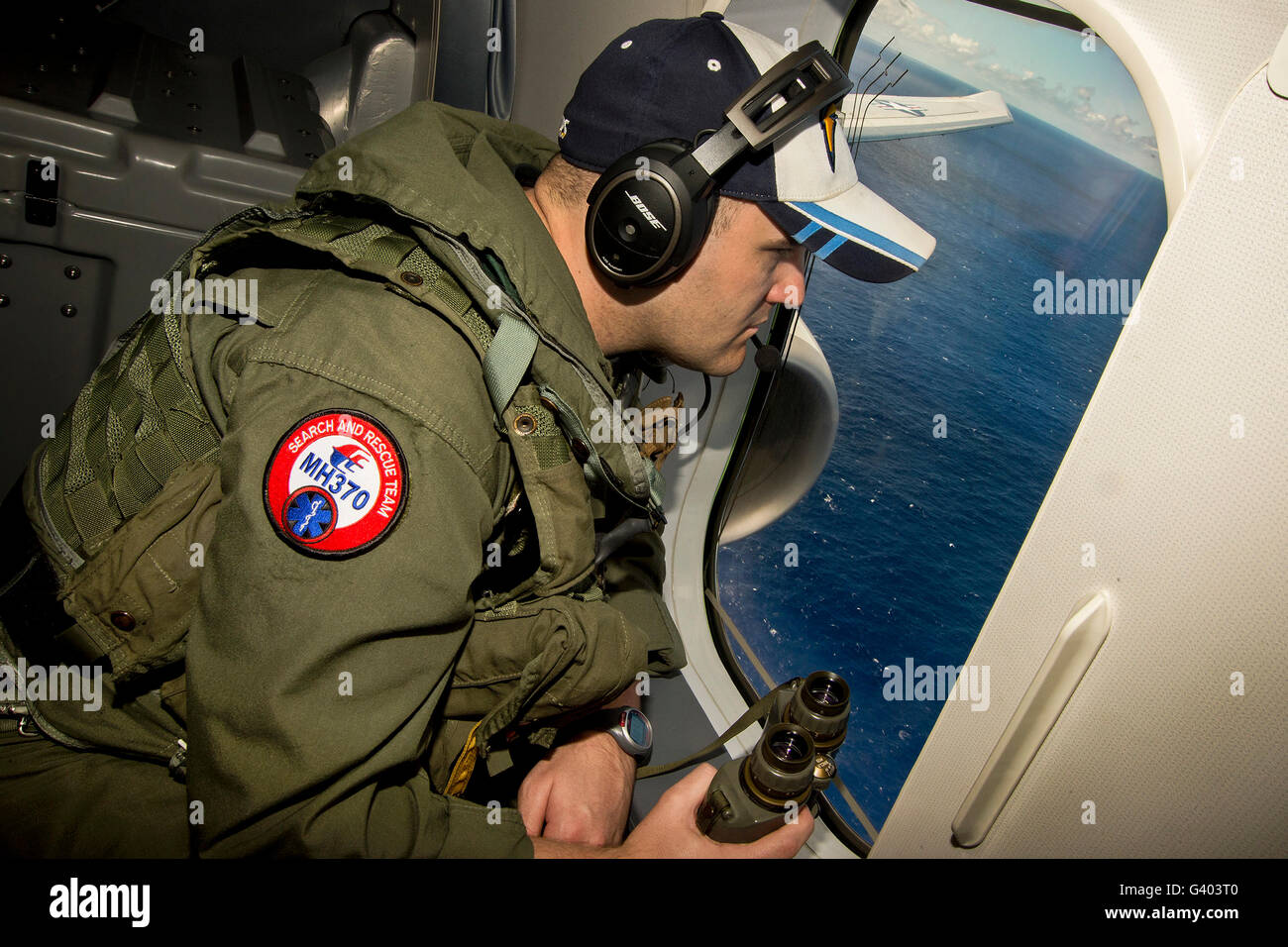 Naval Aircrewman searches out the window of a P-8A Poseidon. - Stock Image