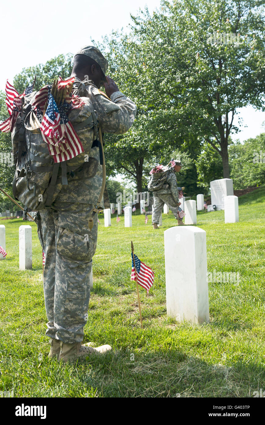 U.S. Army Soldiers place flags in front of the gravesites in Arlington National Cemetery. - Stock Image