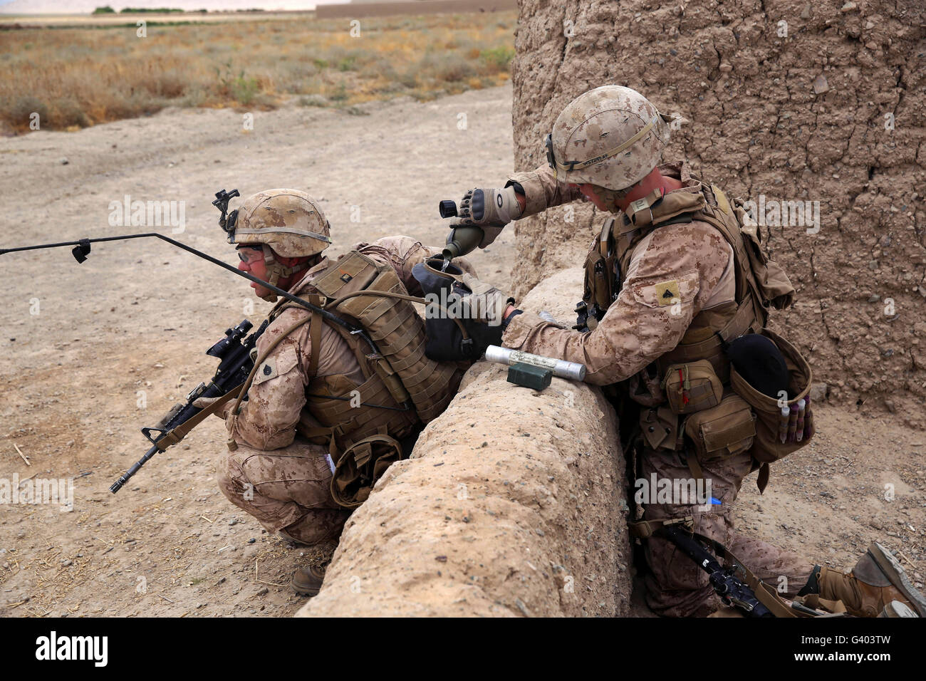 U.S. Marine fills a Camelbak bladder with water for a fellow Marine. - Stock Image