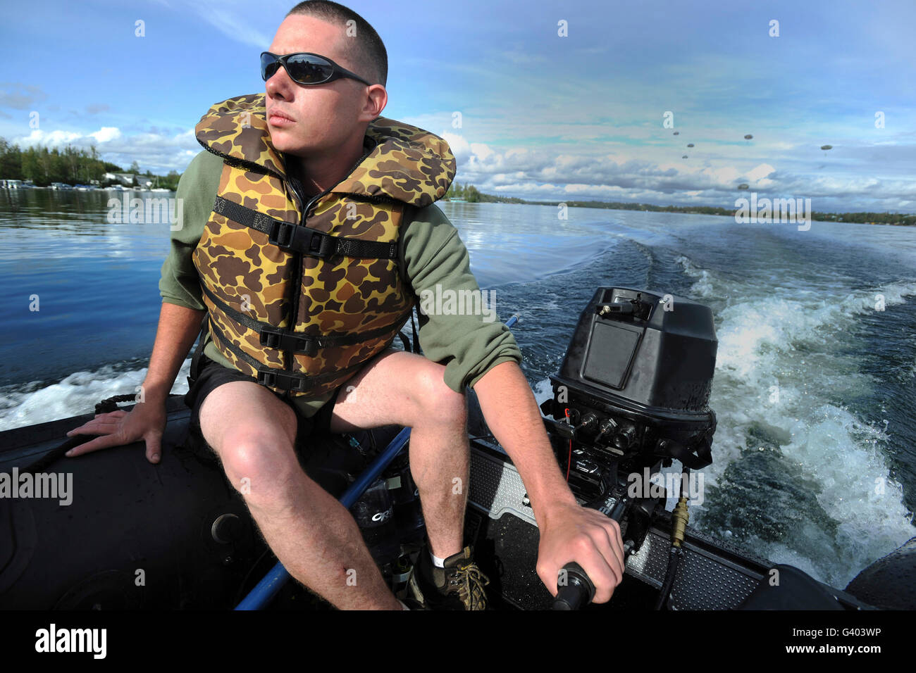 U.S. Army Soldier pilots a Zodiac boat in Big Lake, Alaska. - Stock Image
