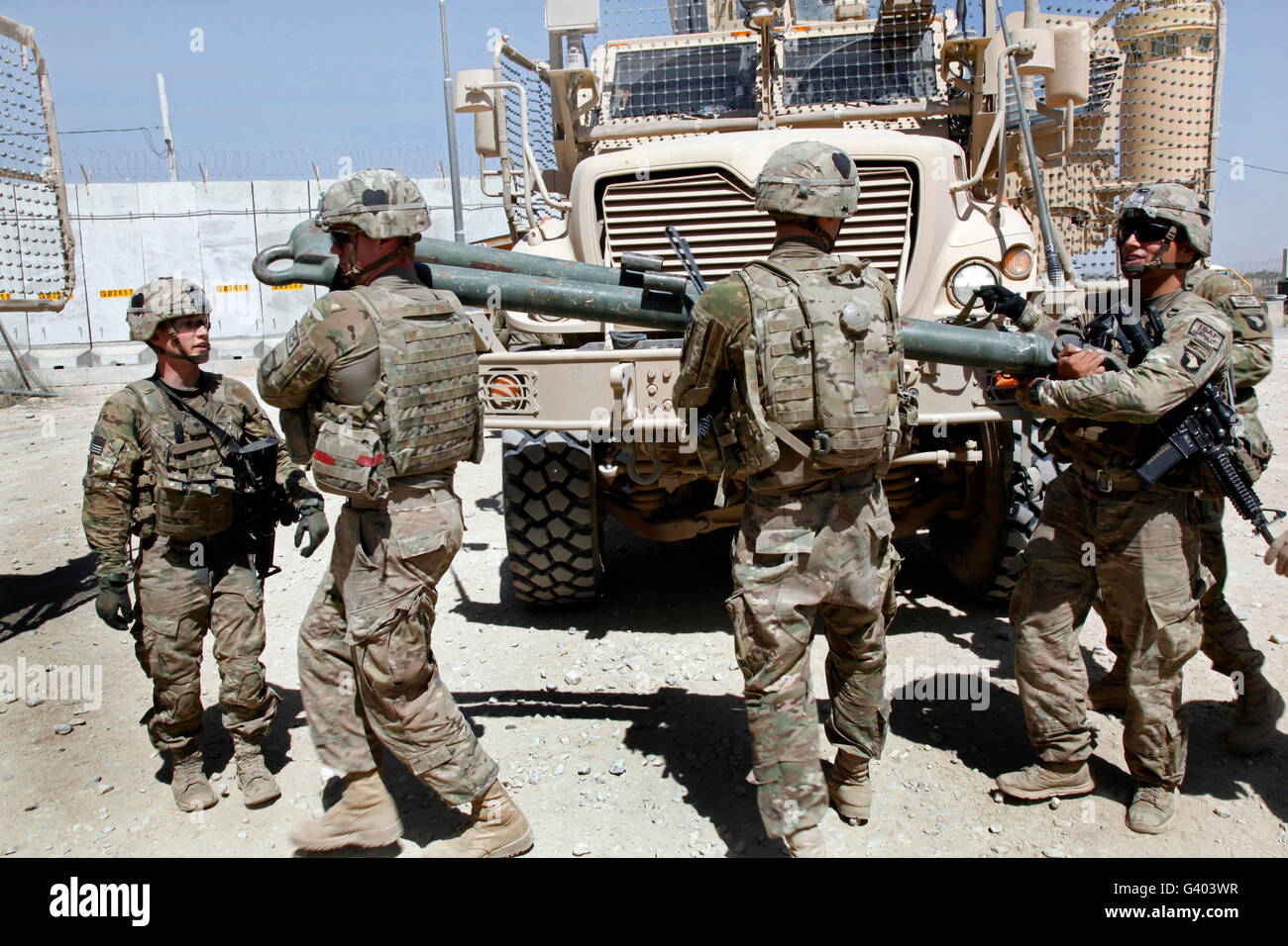 U.S. soldiers move a tow bar from one vehicle to another. - Stock Image