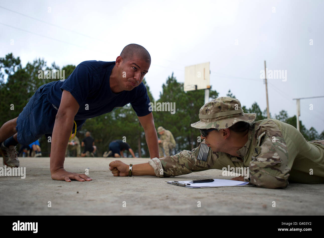 A TIGRES commando conducts push-ups in front of a Green Beret. - Stock Image