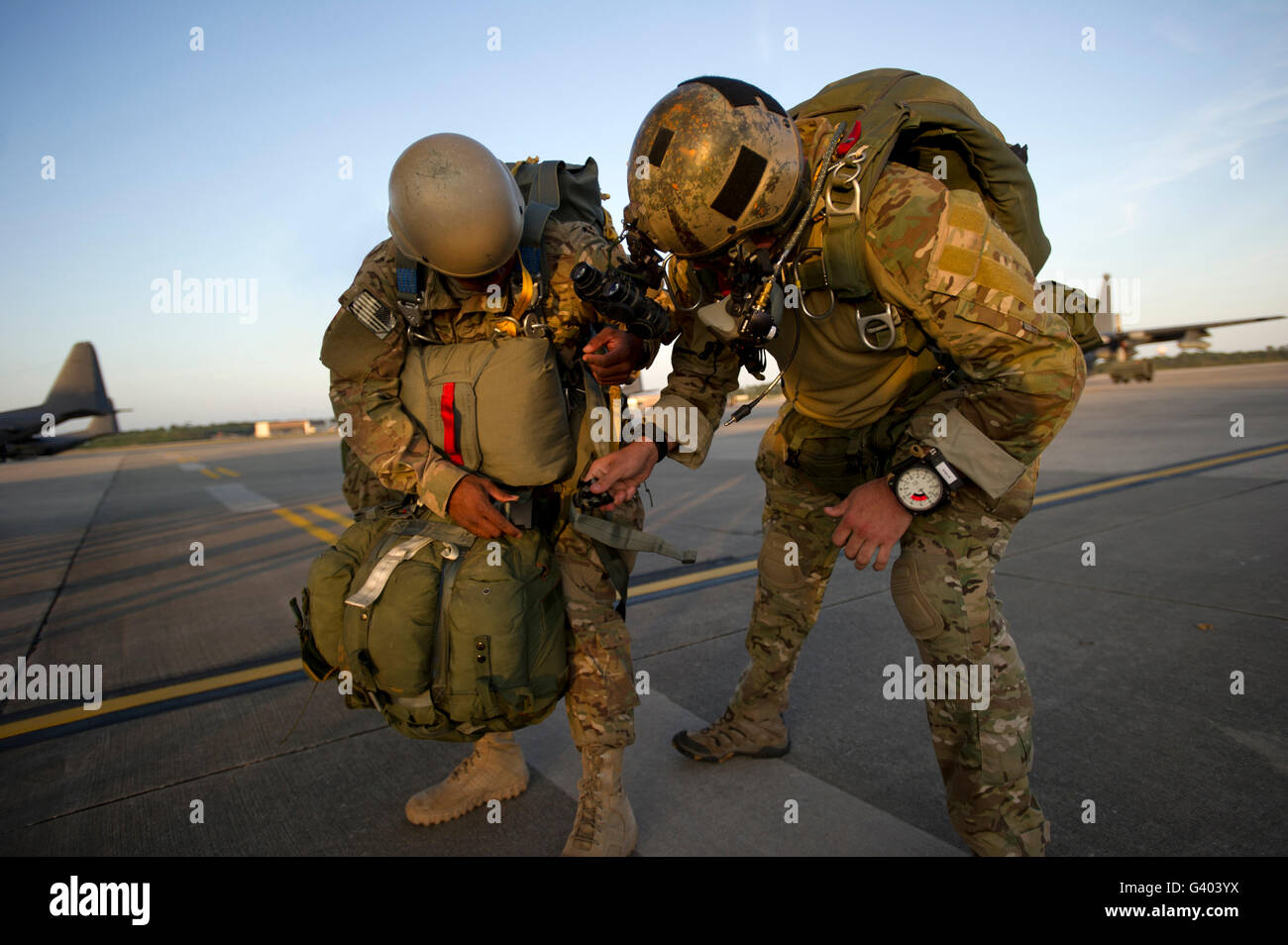 A Green Beret inspects the gear on a static line jumper. - Stock Image