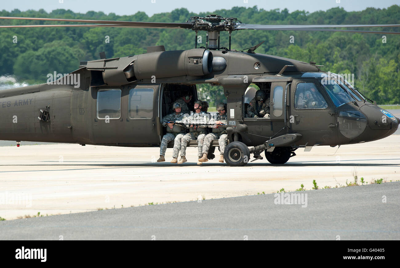 National Guard Special Forces Soldiers sit with their legs hanging outside of a UH-60. - Stock Image
