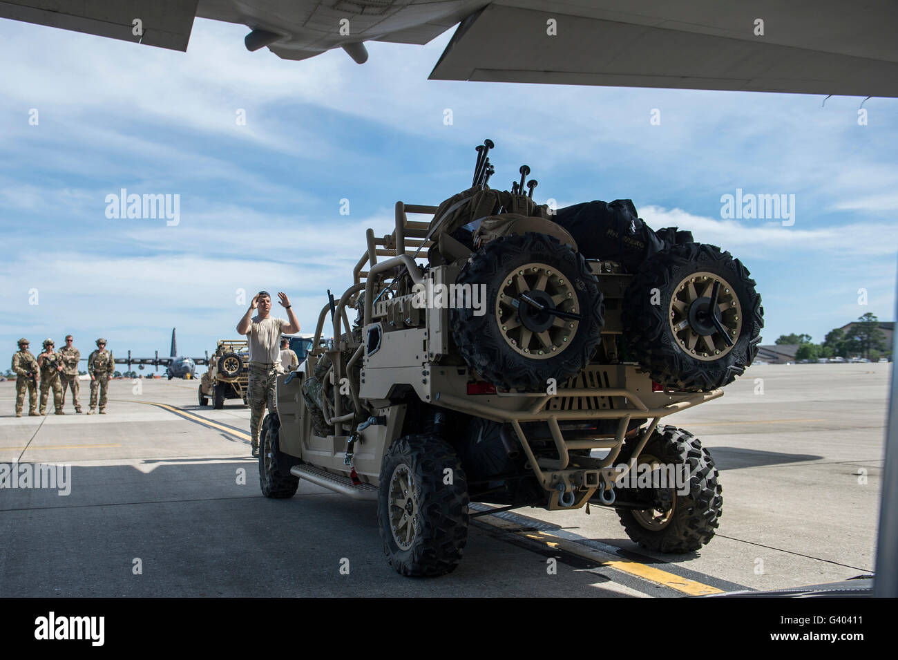 An all-terrain vehicle is guided onto a C-130 Hercules. - Stock Image