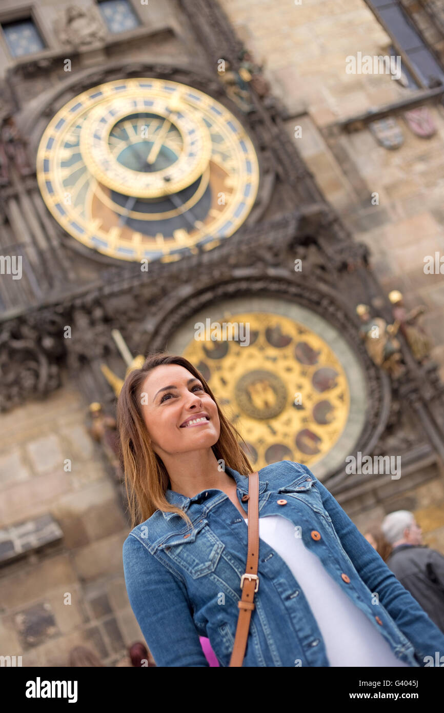 young woman in prague with the astronomical clock behind her - Stock Image
