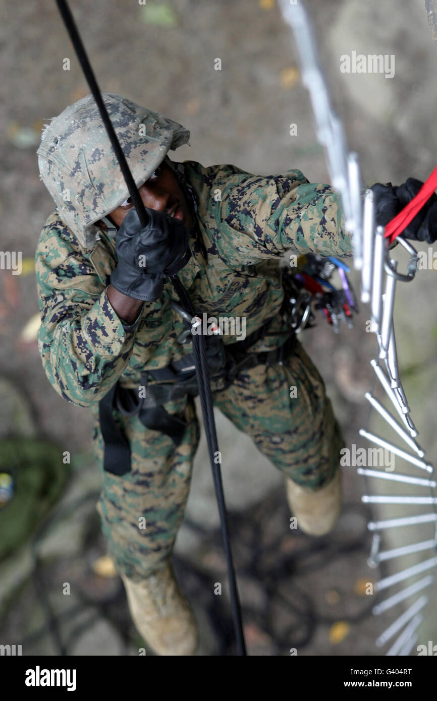 A soldier prepares a cable ladder fixed lane on the side of a 45-foot cliff. - Stock Image