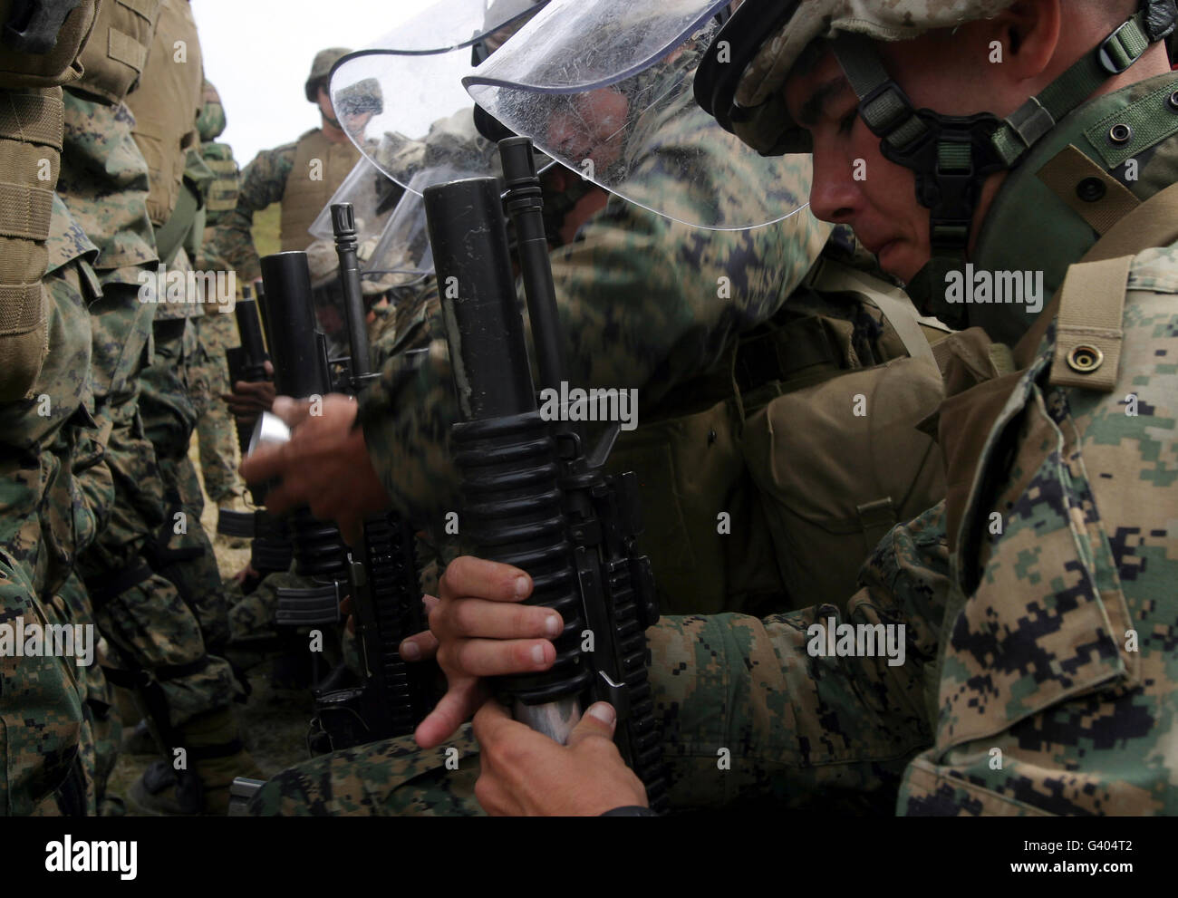 A rifleman loads a foam baton round into his M203 grenade launcher. - Stock Image