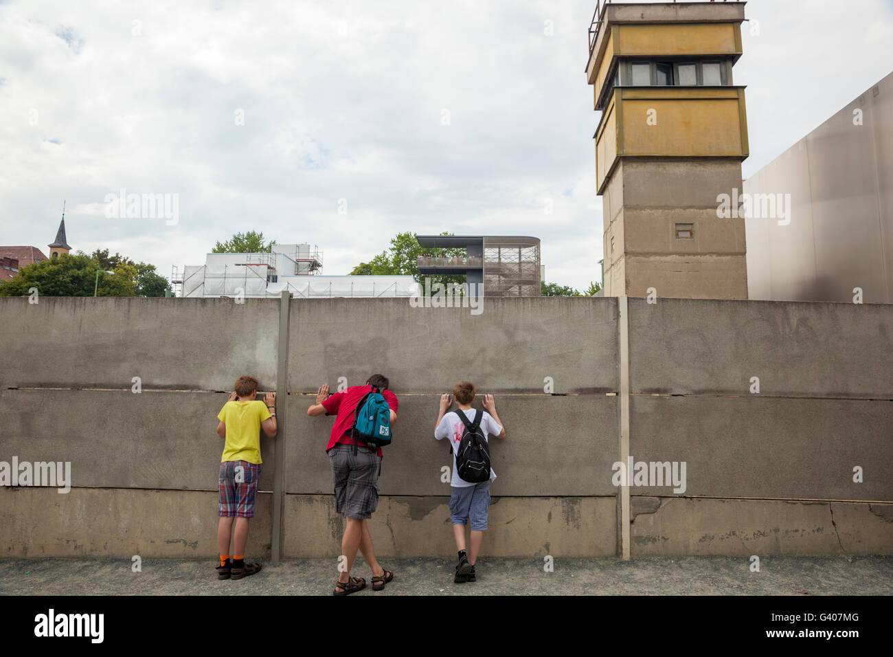 A family peeking through the Berlin wall memorial. - Stock Image