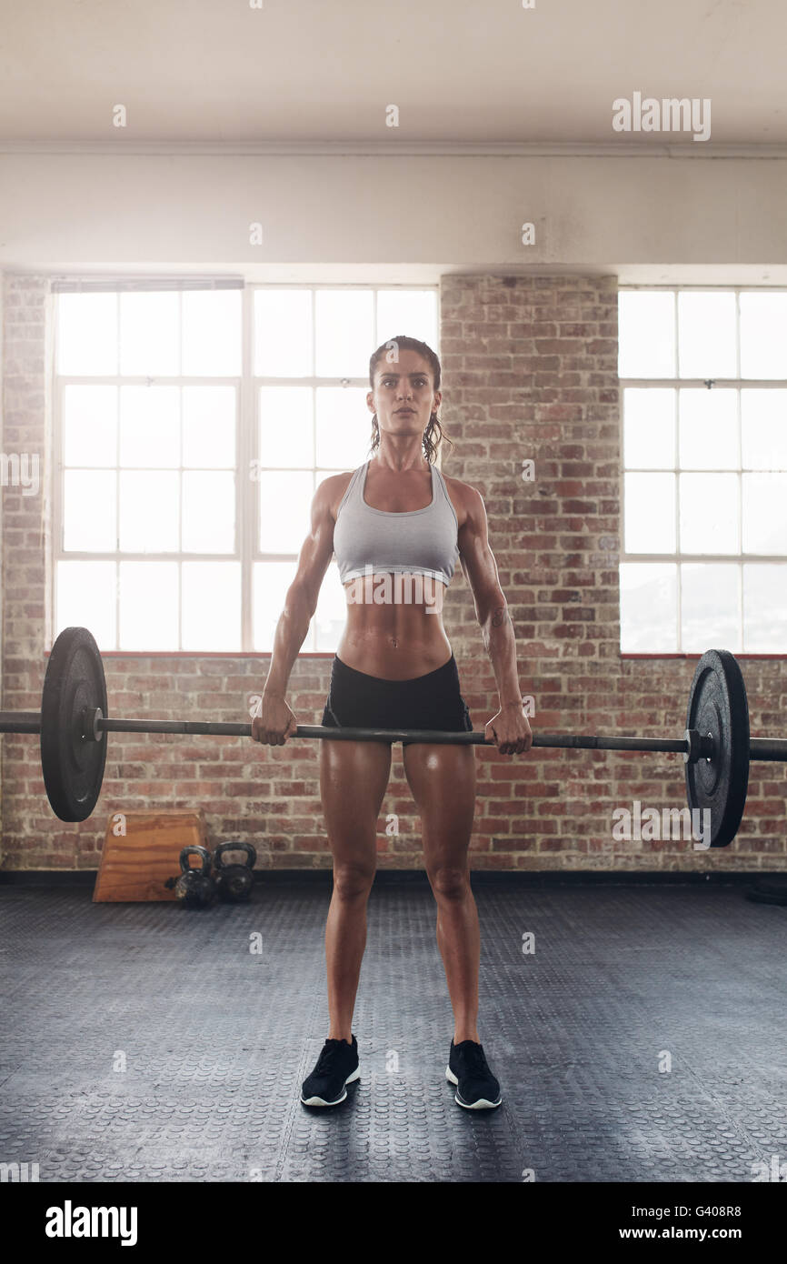 Fit young female athlete lifting heavy weights. Fitness  model performing crossfit exercise at gym. - Stock Image