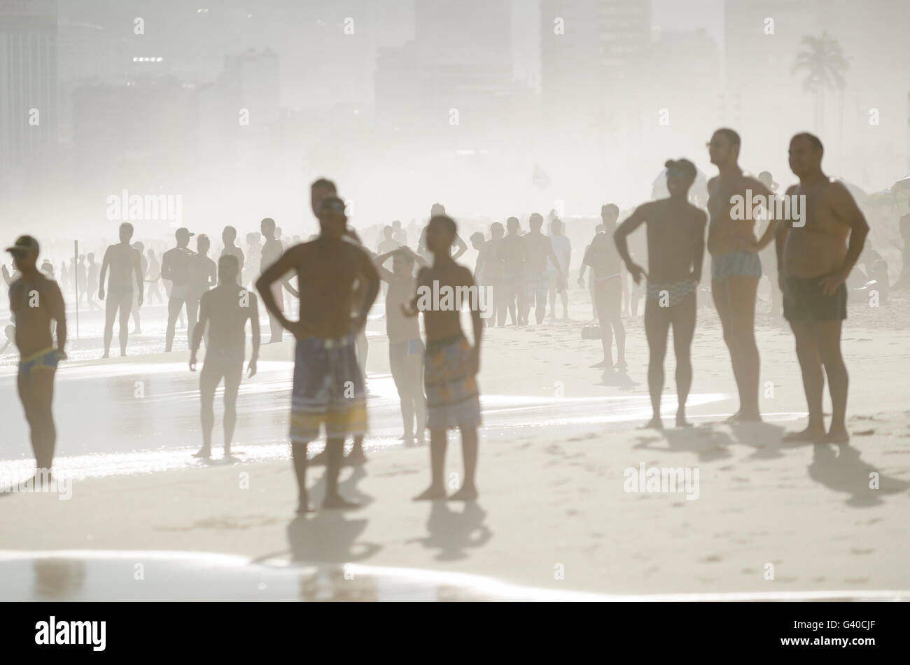 RIO DE JANEIRO - JANUARY 20, 2014: Silhouettes of beachgoers fill the shore of Ipanema at sunset on a summer afternoon. - Stock Image