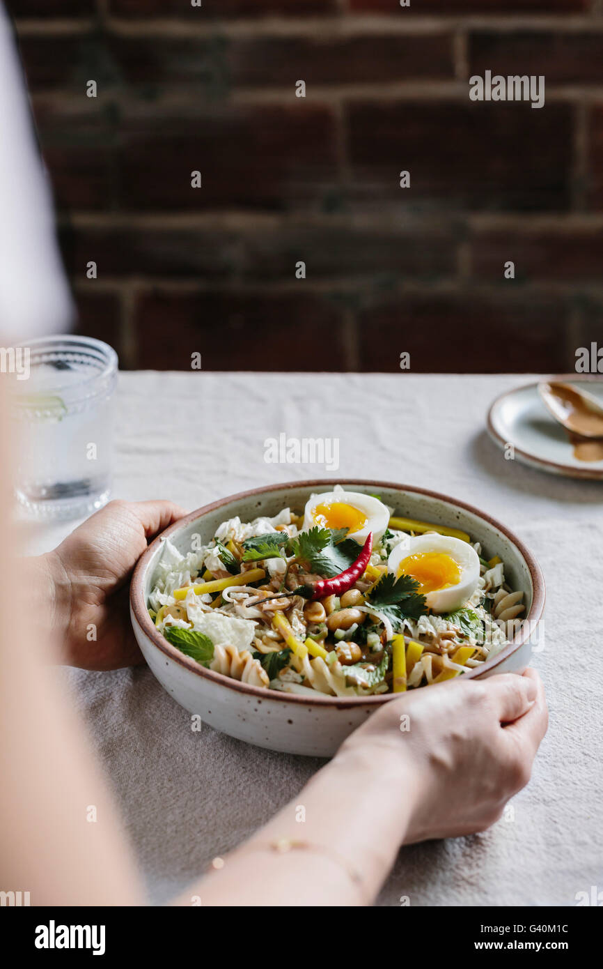 A woman is photographed while she is placing a veggie bowl on the table. - Stock Image