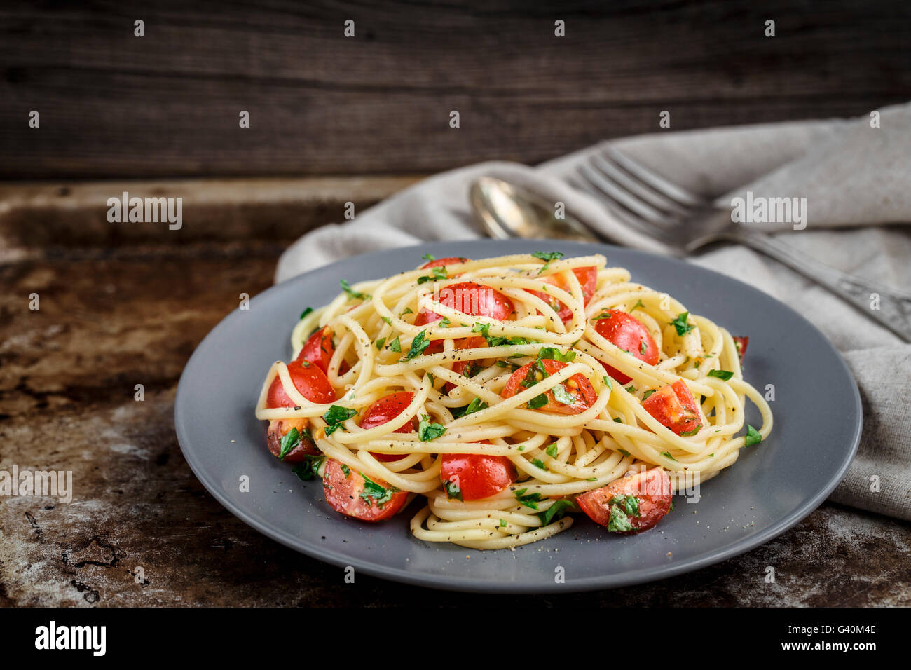 Spaghetti pasta with cherry tomatoes and parsley on rustric background - Stock Image
