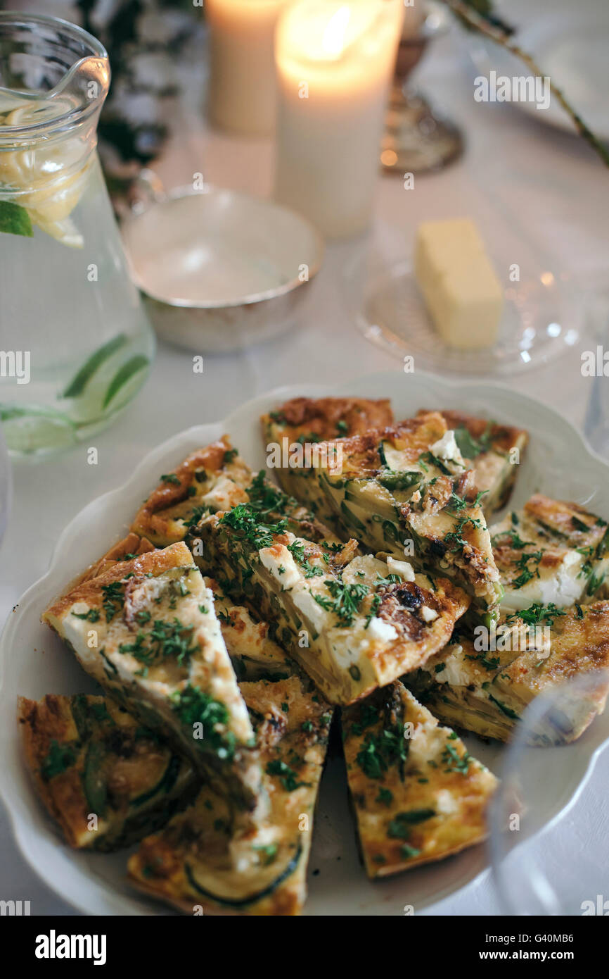 Frittata with vegetables and goat cheese and a glass jar of lemon and lime infused water on a set up table for light - Stock Image