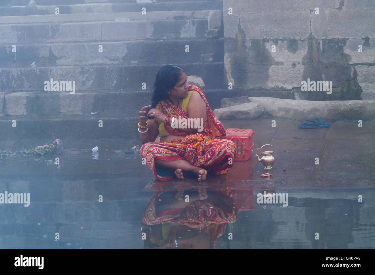 Unidentified Indian woman taking ritual bath in the river Ganges at cold foggy winter morning. Stock Photo