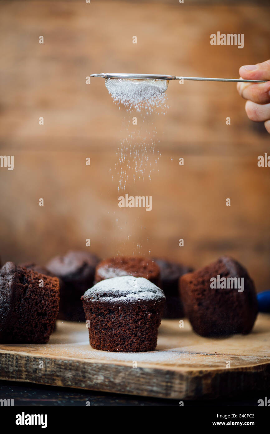 Hand sifting powdered sugar on chocolate muffins using a tea strainer. - Stock Image