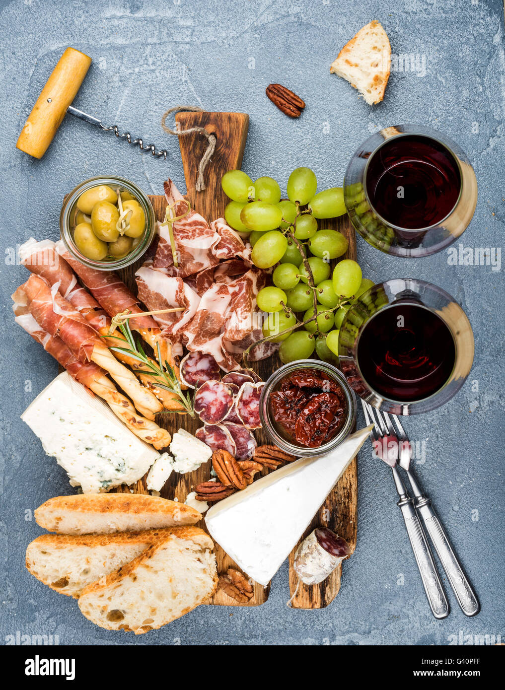 Cheese and meat appetizer selection. Prosciutto di Parma, salami, bread sticks, baguette slices, olives, sun-dried - Stock Image