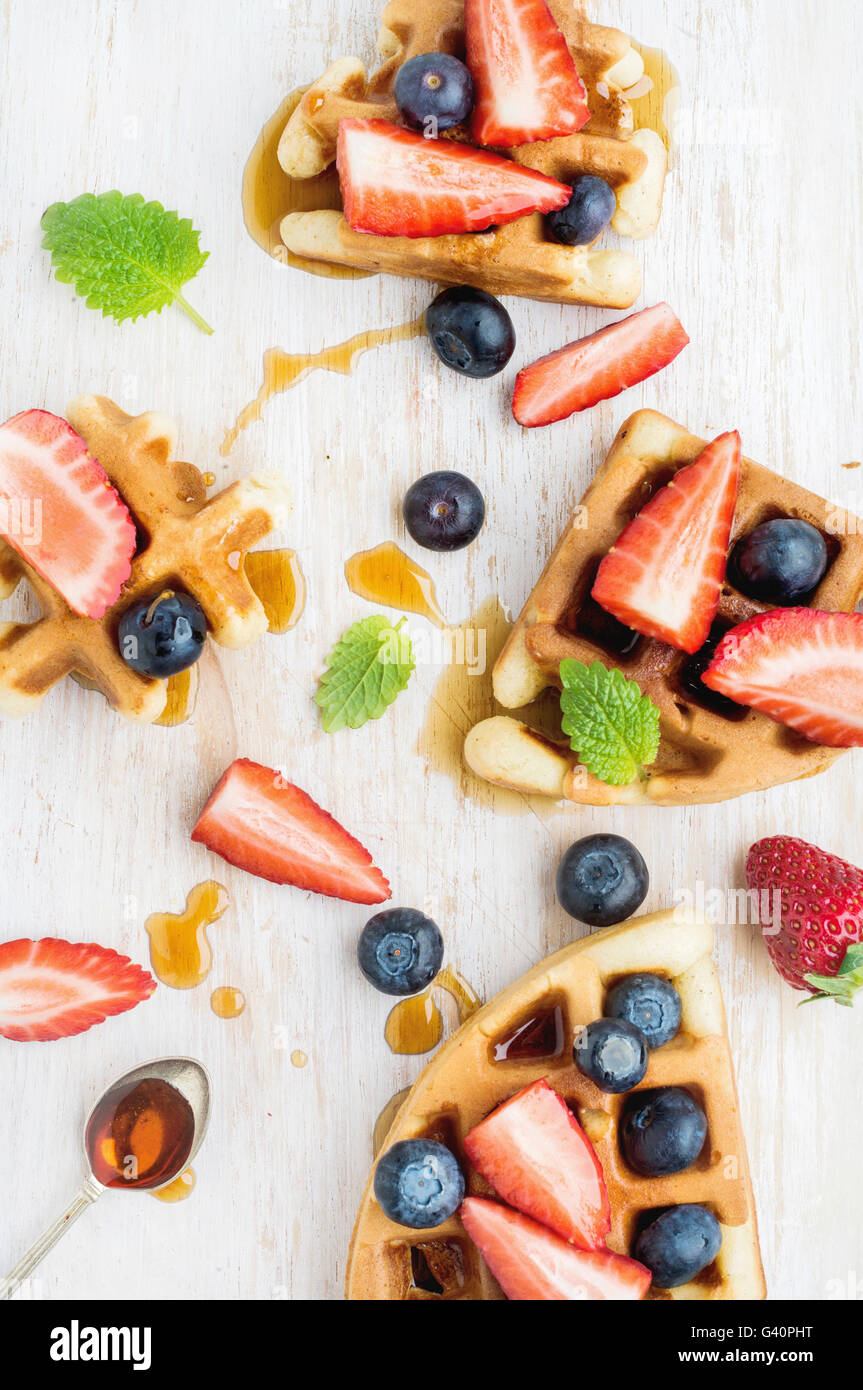 Home made Belgian waffles served on a white woodenl tray with berries , marple syrup and mint leaves, top view - Stock Image