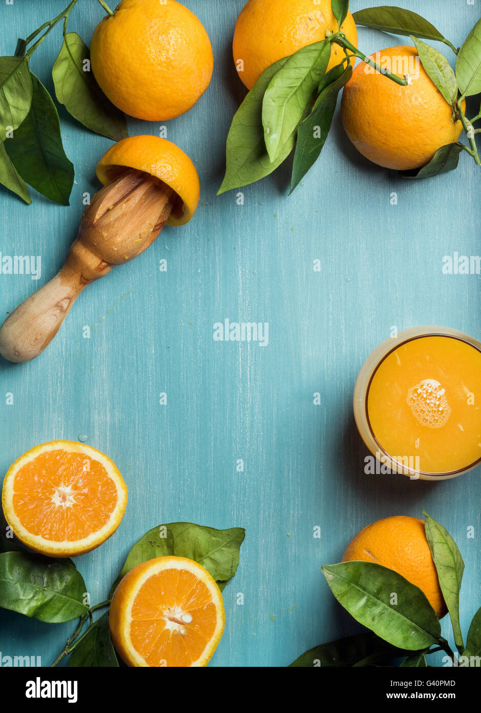 Fresh orange juice in glass and oranges with leaves on wooden turquoise blue painted background. Top view, copy - Stock Image