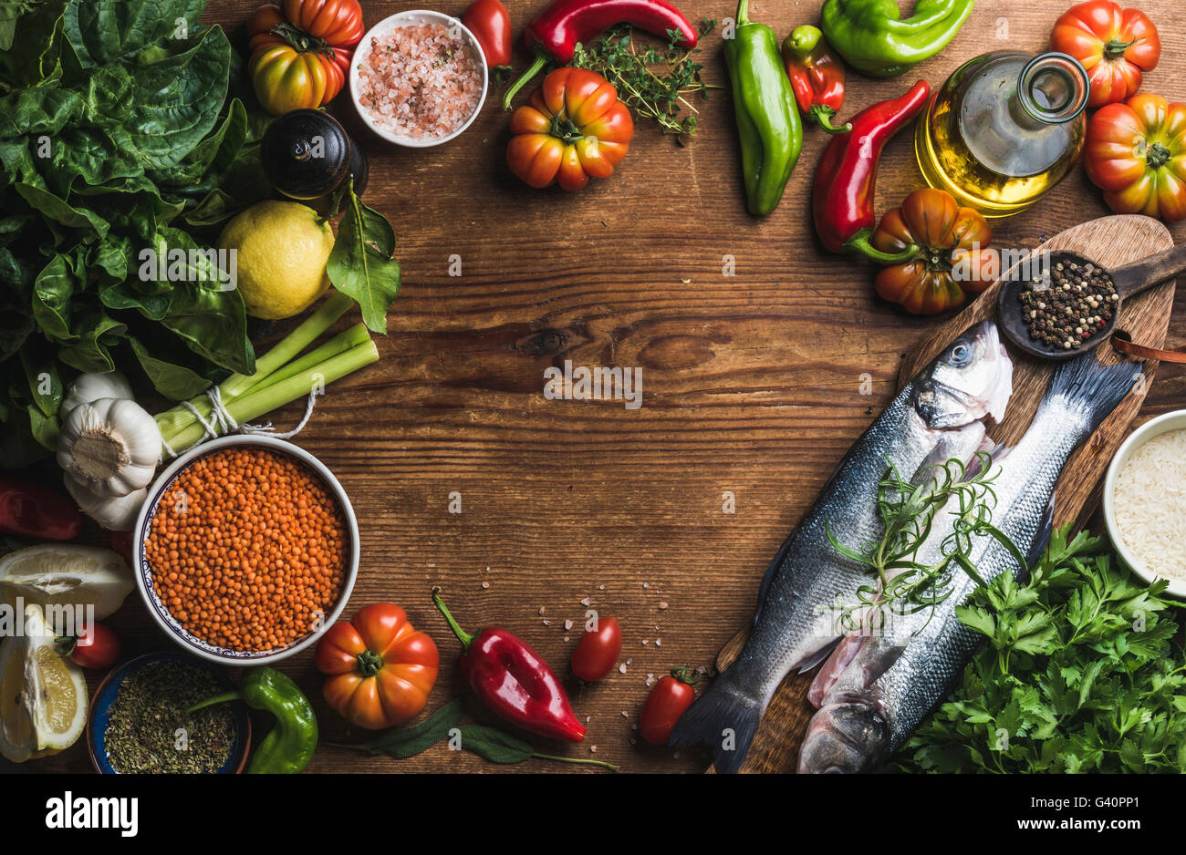 Ingredients for cooking healthy dinner. Raw uncooked seabass fish with vegetables, grains, herbs and spices over - Stock Image
