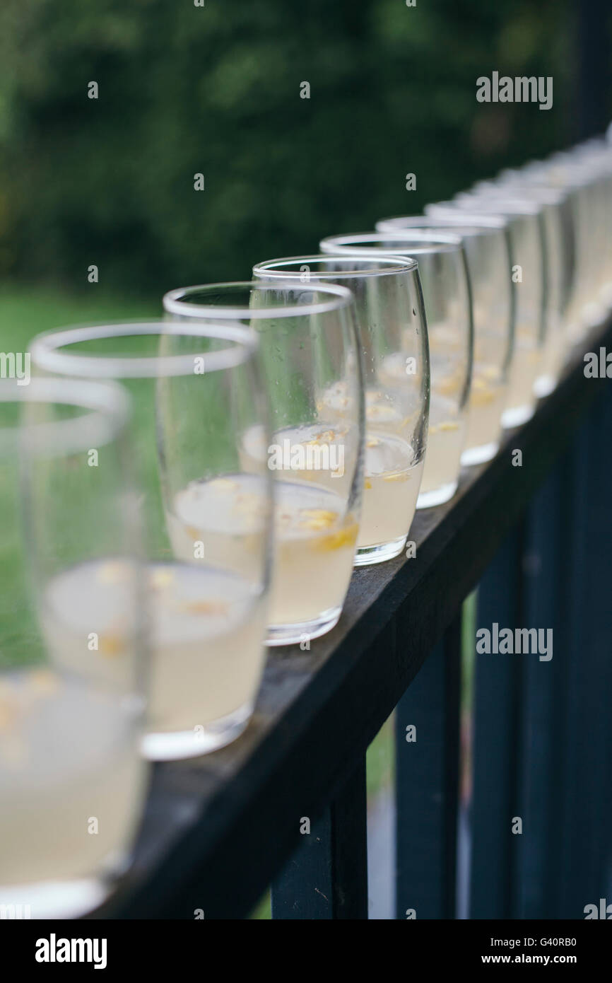 Cocktails with fresh edible flowers in glasses lined on the fence outside - Stock Image