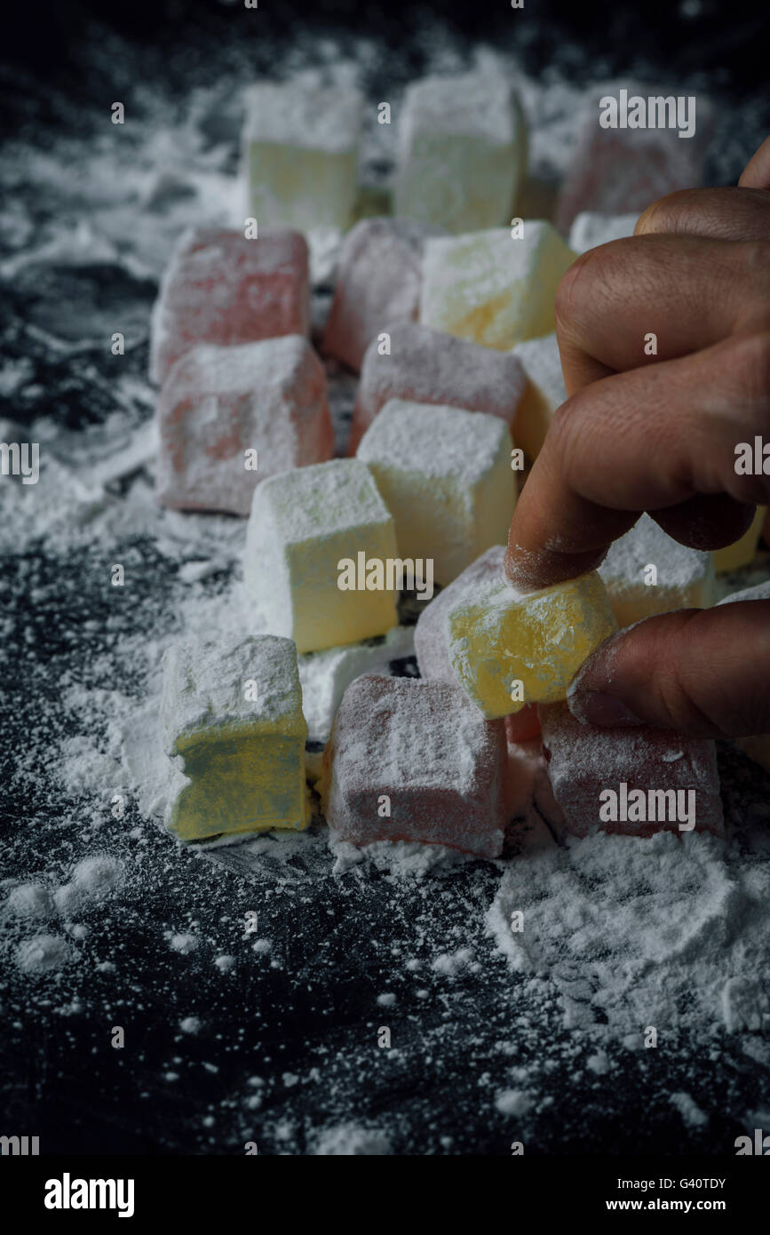 A hand is grabbing a classic Turkish delight. - Stock Image