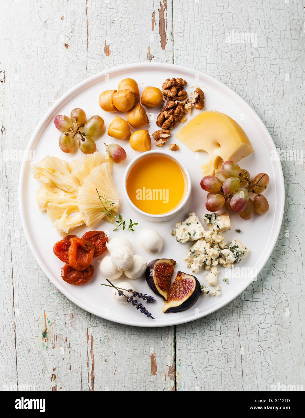 Cheese plate Snacks assortment with honey on white plate - Stock Image