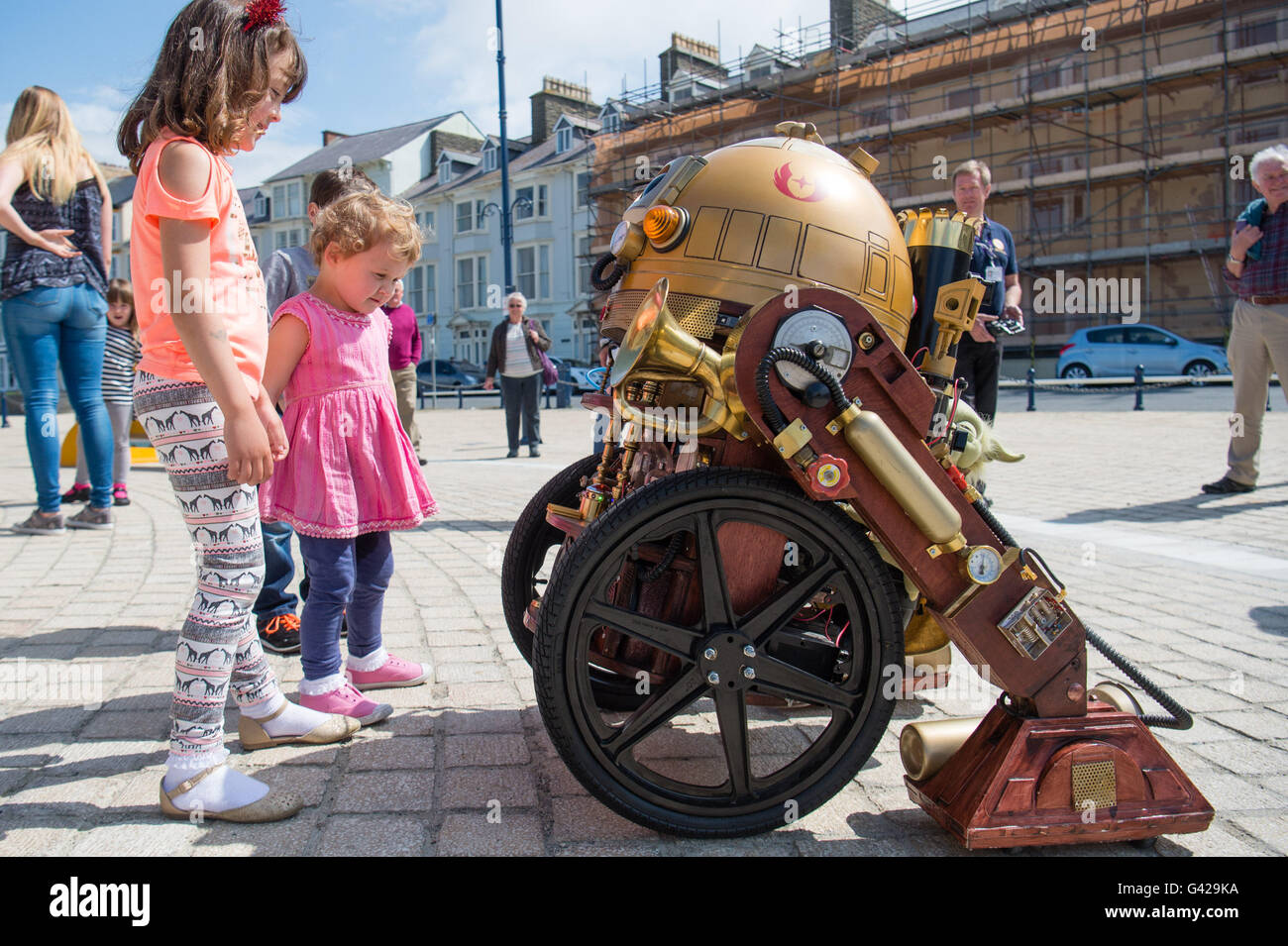 Aberystwyth Wales UK, Saturday 18 June 2016 Children interacting with a 'steam punk RD-D2' replica robot on a bright Stock Photo