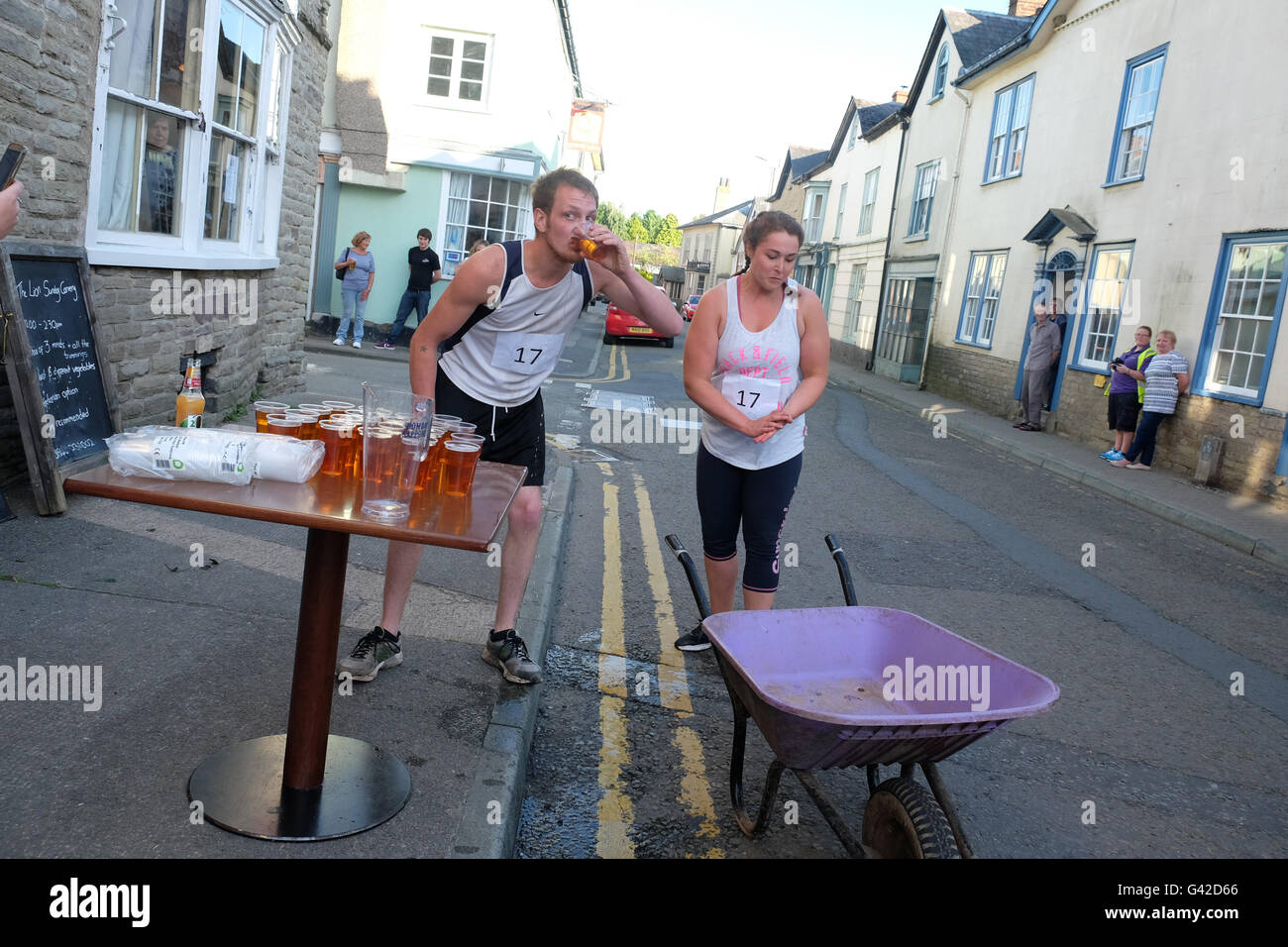 Kington, Herefordshire, UK - Saturday 18th June 2016 - A man and woman team stop for the next beer as they take - Stock Image
