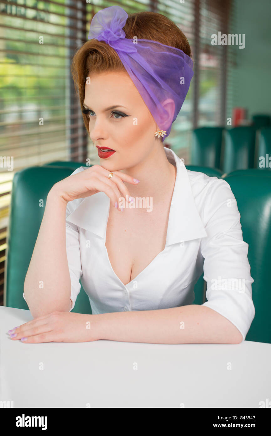 1960s look pin up girl in an American diner, looking serious - Stock Image