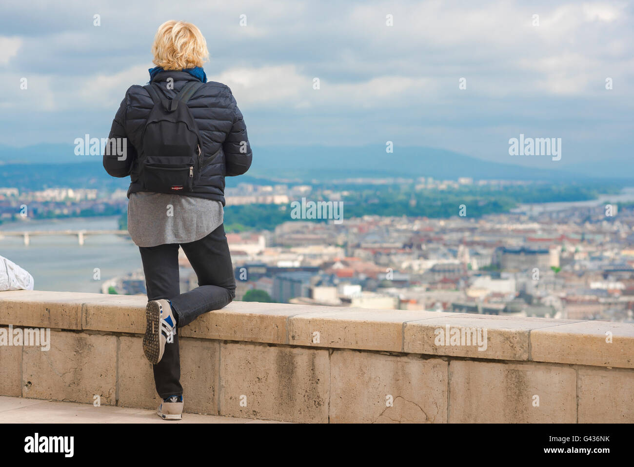 A young female tourist wearing a backpack surveys the centre of Budapest from the top of Gellert-hegy (hill) on Stock Photo