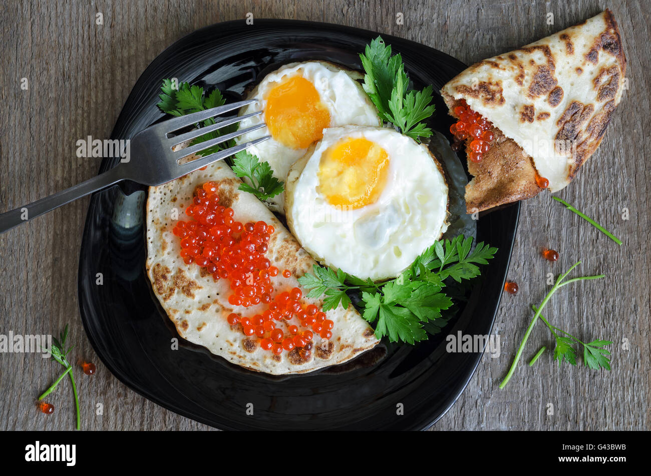 Scrambled eggs and pancakes with caviar on a black plate - Stock Image