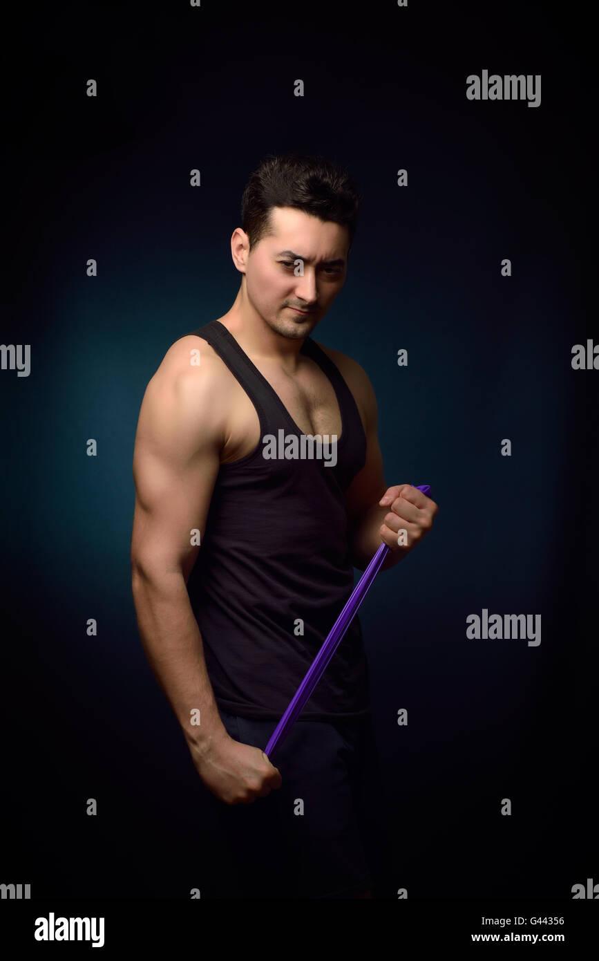 Muscle man training on dark background - Stock Image