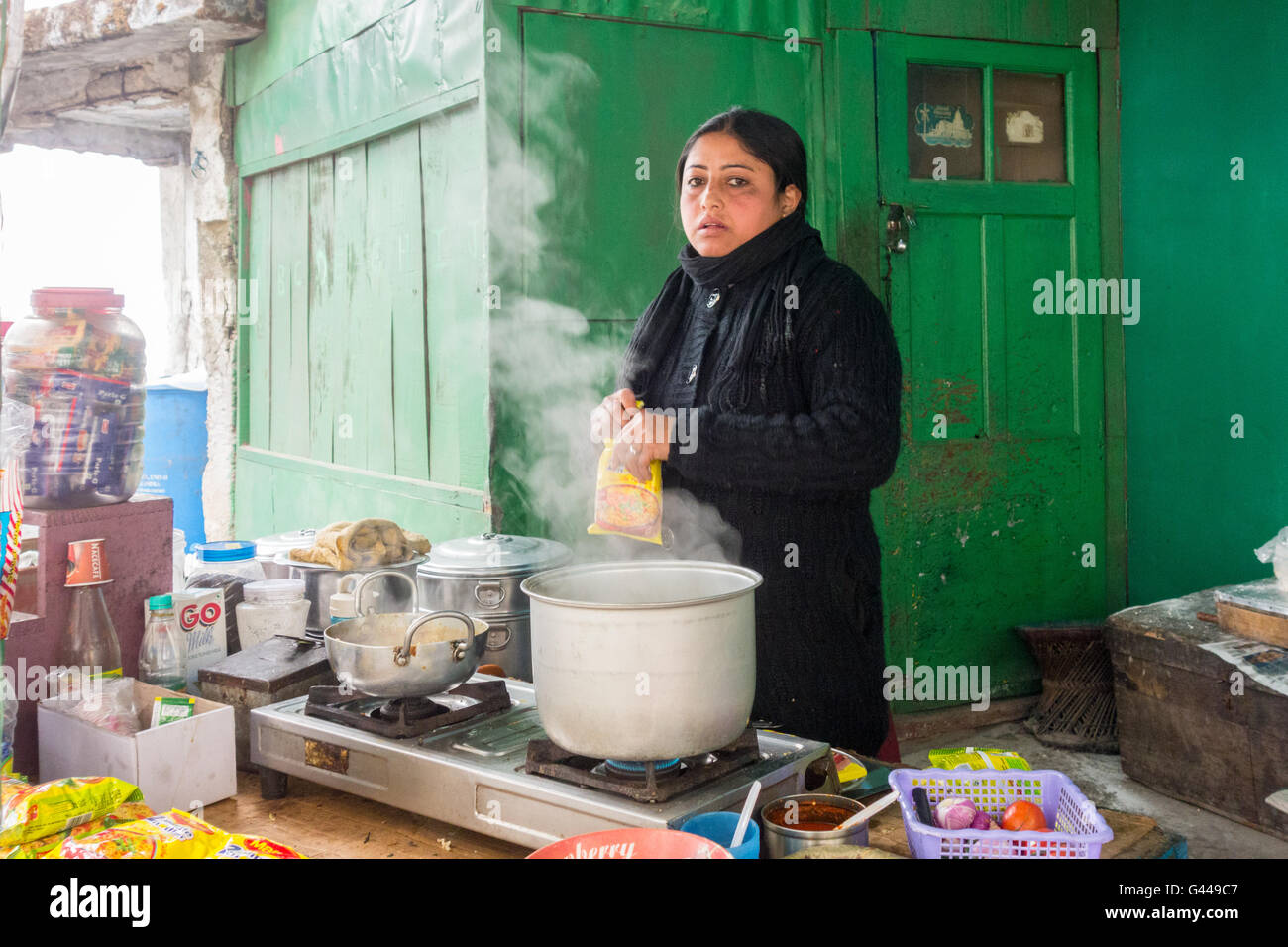 A woman cooking Maggi noodles outside her house for customers at the boarding point of Darjeeling Ropeway in West - Stock Image