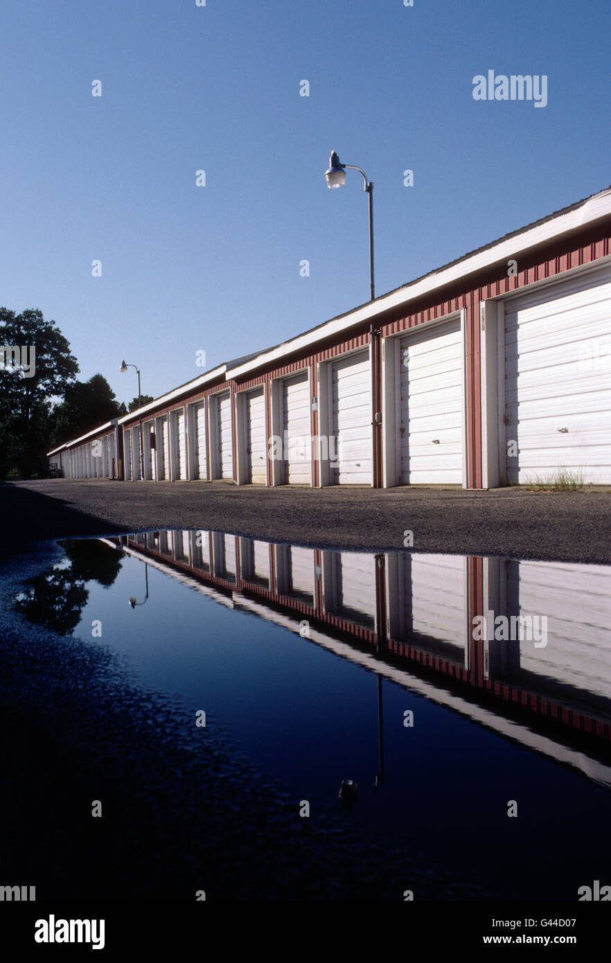 Daytime view of garage like rental storage units lined up in a row - Stock Image